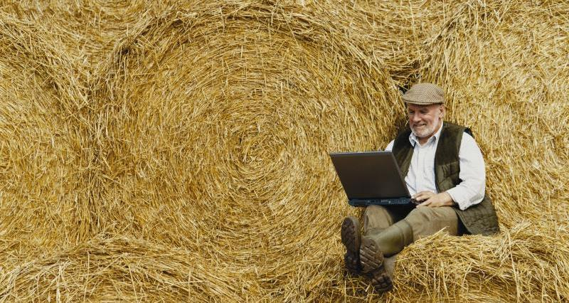 Farmer with laptop on straw bales_9339
