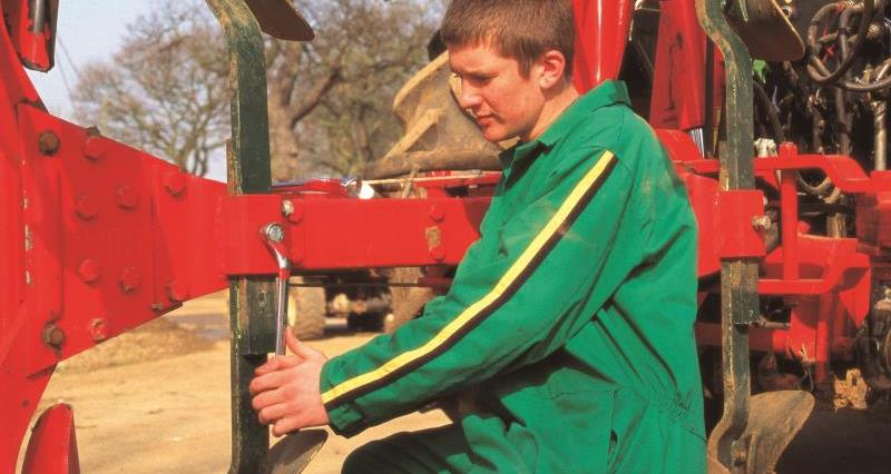 Young farmer adjusting machinery_7775