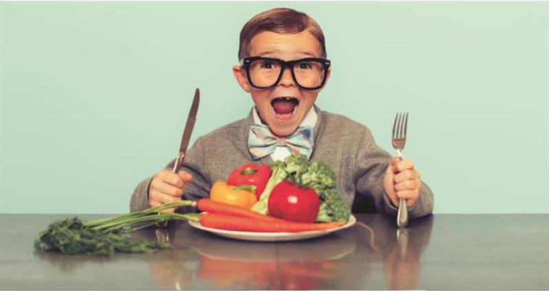 Young boy looking happy, holding a knife and fork with a large plate of vegetables in front of him