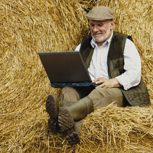 Farmer with laptop on hay bales, square, 300px_21034