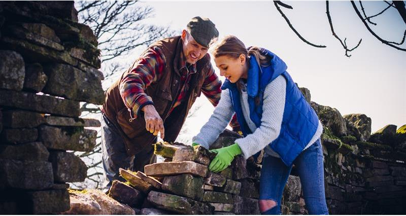 young woman and man building dry stone wall, employment, labour_59809