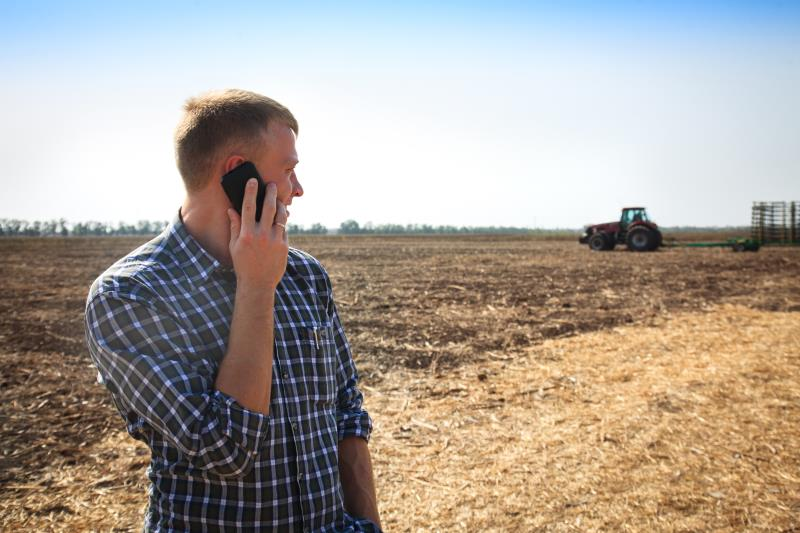 iStock man on phone in field with tractor_50839